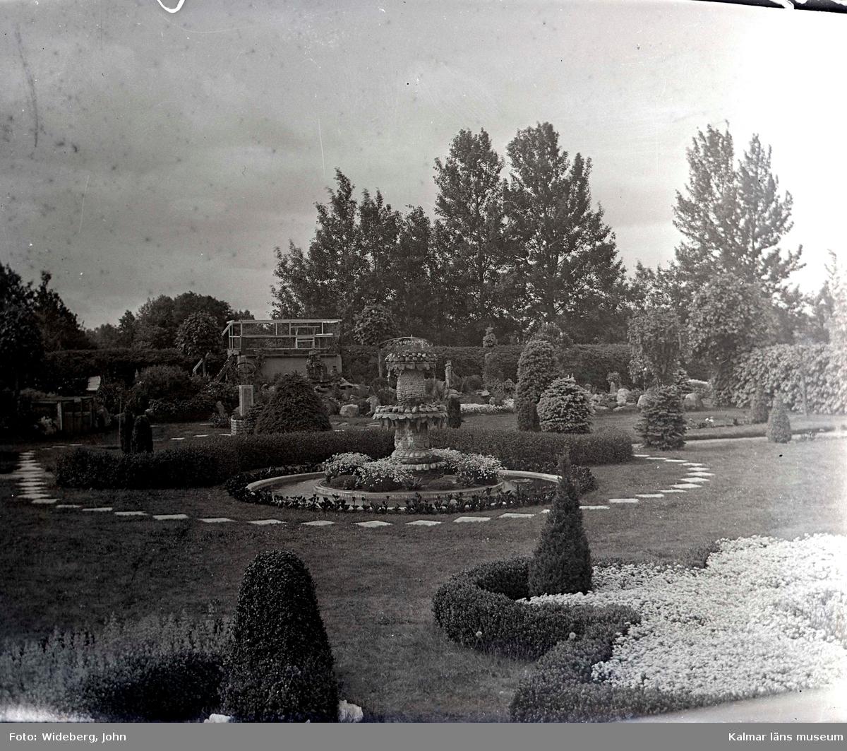 Utsiktsplatsen (södra delen) i Widebergs trädgård.  John Wideberg blev tidigt intresserad av trädgårdsanläggningar. Han hade sannolikt hämtat inspiration på resor han gjort till Stockholmsutställningen 1897 och till Göteborg 1923. Han blev också vän med stadsträdgårdsmästaren Haglund i Kalmar. John hade palmer i potatiskällaren under huset och påfåglar, ekorrar och pärlhöns som övervintrade i hönshuset. En papegoja och en sköldpadda fick tillbringa vintrarna inne i köket. Runt trädgården planterade han skyddande häckar. Arbetet påbörjades redan när han var 18 år med att han hämtade åtta granar i skogen, och planterade dem i en ring mitt i trädgården. Dessa finns kvar än idag. I slutet av 1930-talet arrenderades jordbruket ut och John kunde ägna sig på heltid åt trädgården, som blev alltmer av ett besöksmål. John började ta inträde, 25 öre. John utvecklade också sin hobby som tavelmålare och som fotograf. Han tog med sin lådkamera under årens lopp hundratals vackra bilder från trädgården, liksom på vyer, hus och människor i takten. Ca 500 av dessa bilder finns bevarade som glasplåtar, skänkta till Kalmar läns museum.