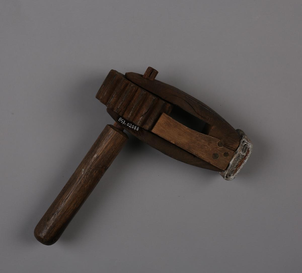 Treskralle/sirene med håndtak og blylodd i ende på skrallen (for å få vekt).