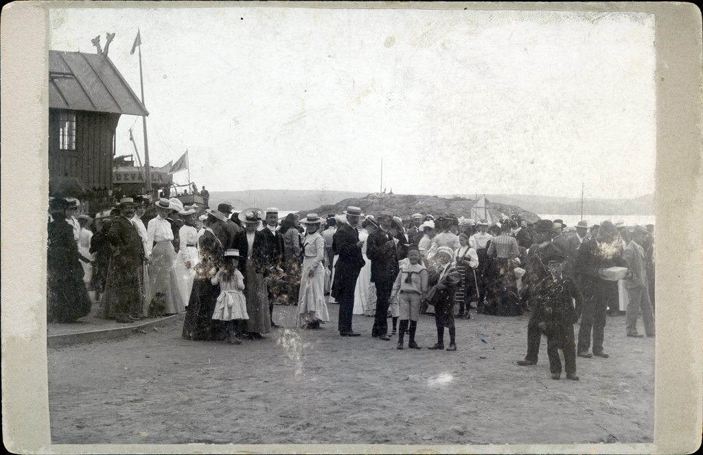 Folksamling i Lyckornas hamn med klocktornet och ångaren Uddevalla till vänster