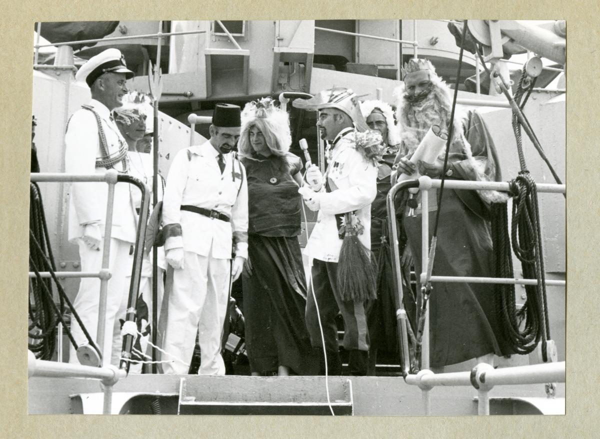 Bilden föreställer en grupp män utklädda till kung Neptun och hans hov under ceremonierna kring ett linjedop ombord på minfartyget Älvsnabben i samband med långresan 1966-1967.