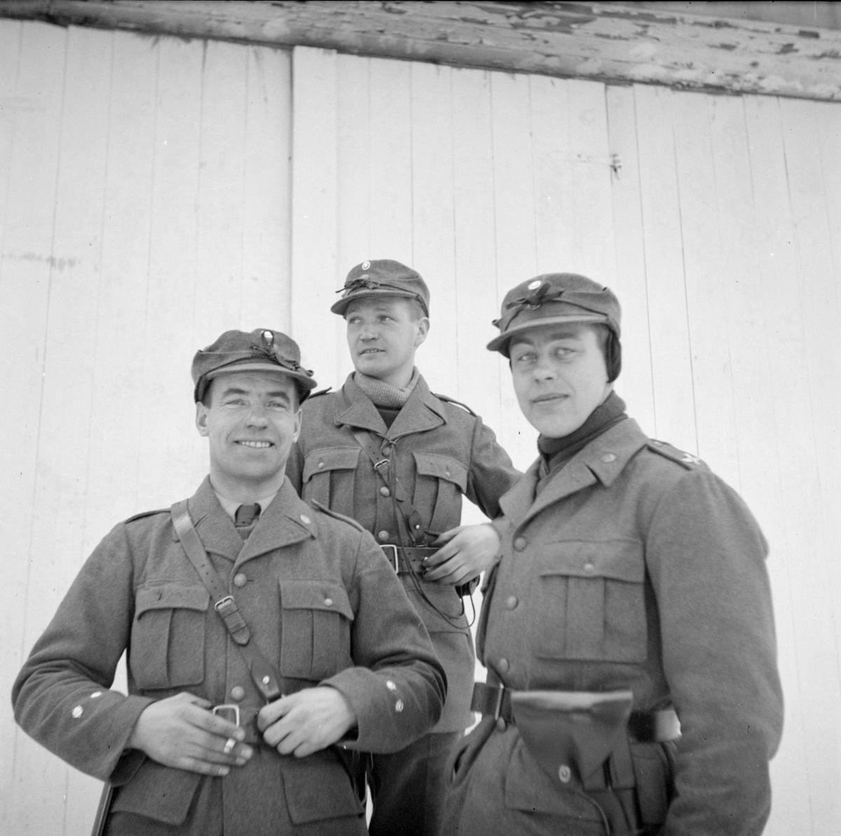 Grupporträtt. Tre militärer tillhörande Svenska frivilligkåren i Finland, F 19, står vid en husvägg.