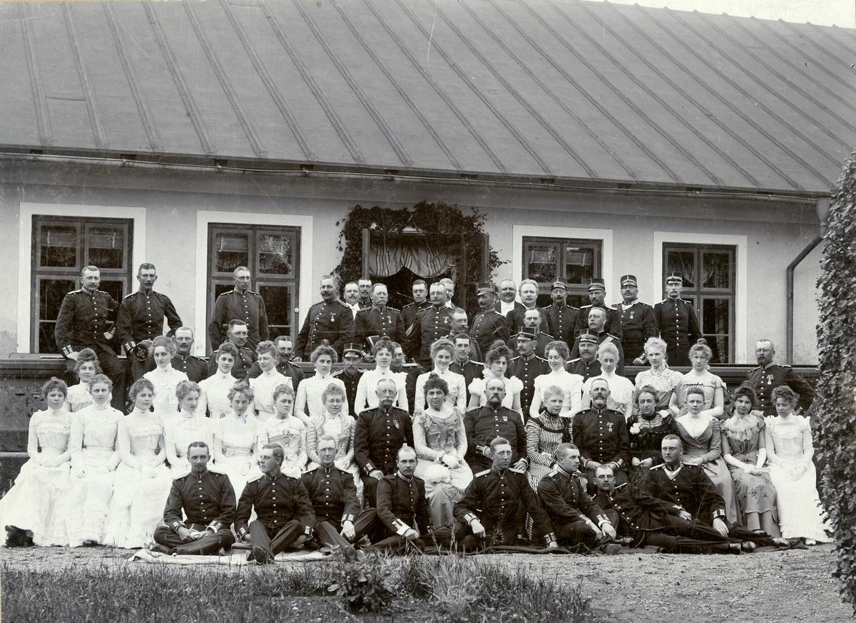 Grupporträtt av officerare från Norra skånska infanteriregementet I 6 med kvinnligt sällskap.