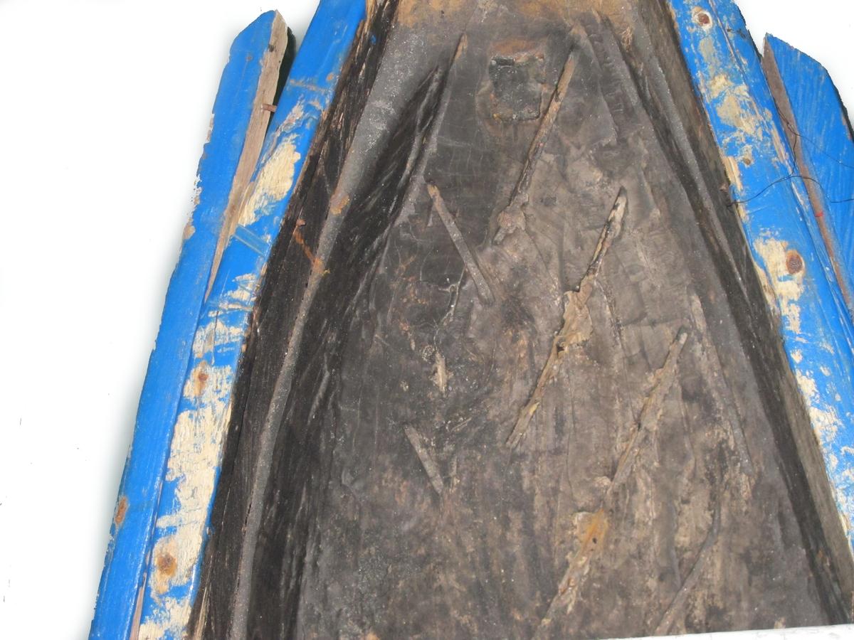 Kano hugget av en tømmerstokk. Hard tropisk tresort. Produksjonen ser ut til å ha foregått med motorsag, (verktøyspor i stevnene og bunnen innvendig). Innskåret tekst på begge sider.