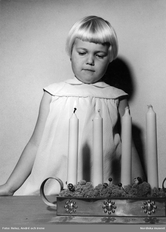 Flicka i ljus klänning vid adventsljusstake