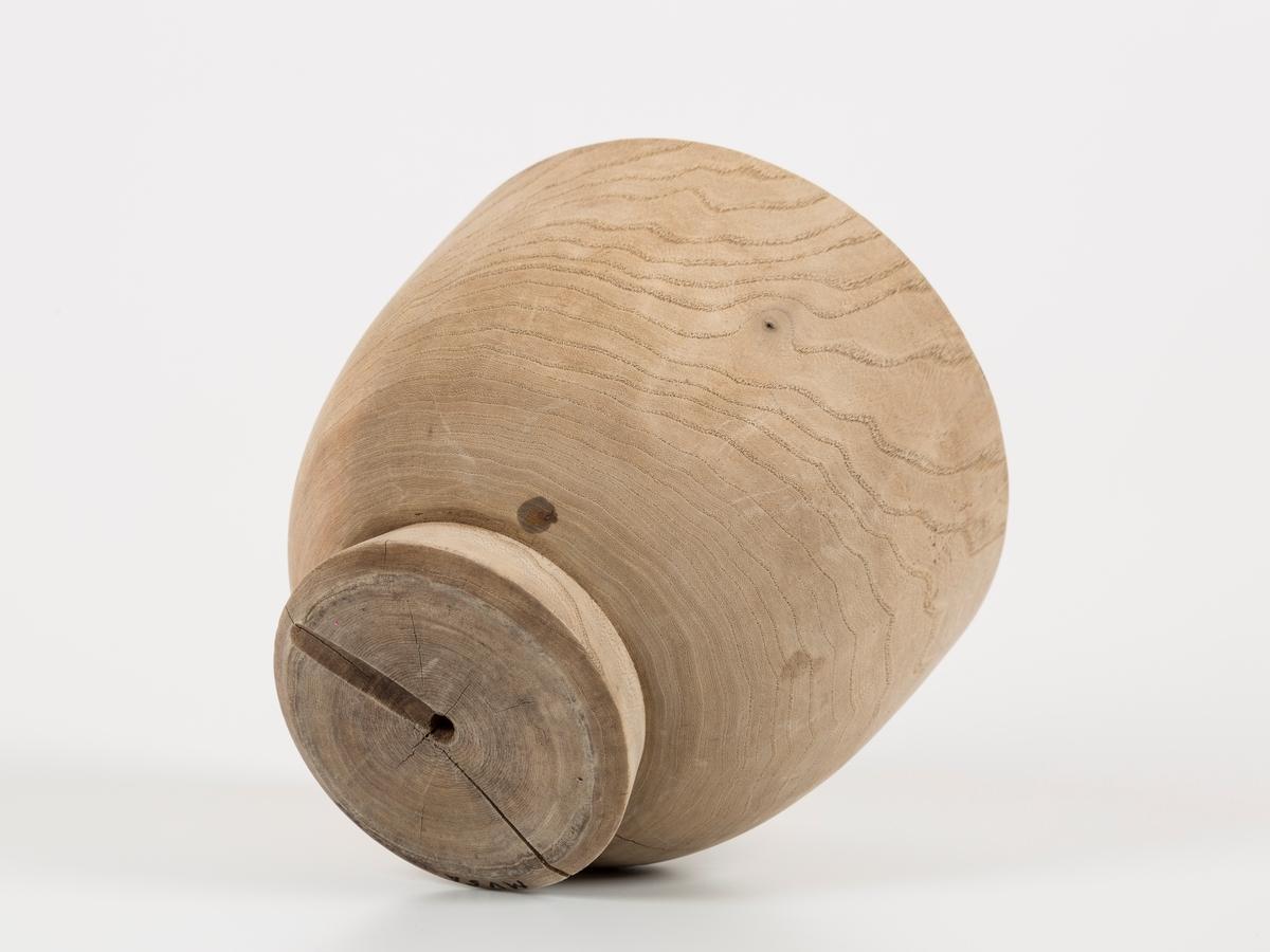 Formen består av to deler: rund bolle og lokk. Lokket er dreiet ut av et stykke eiketre. Lokket er sprukket.
