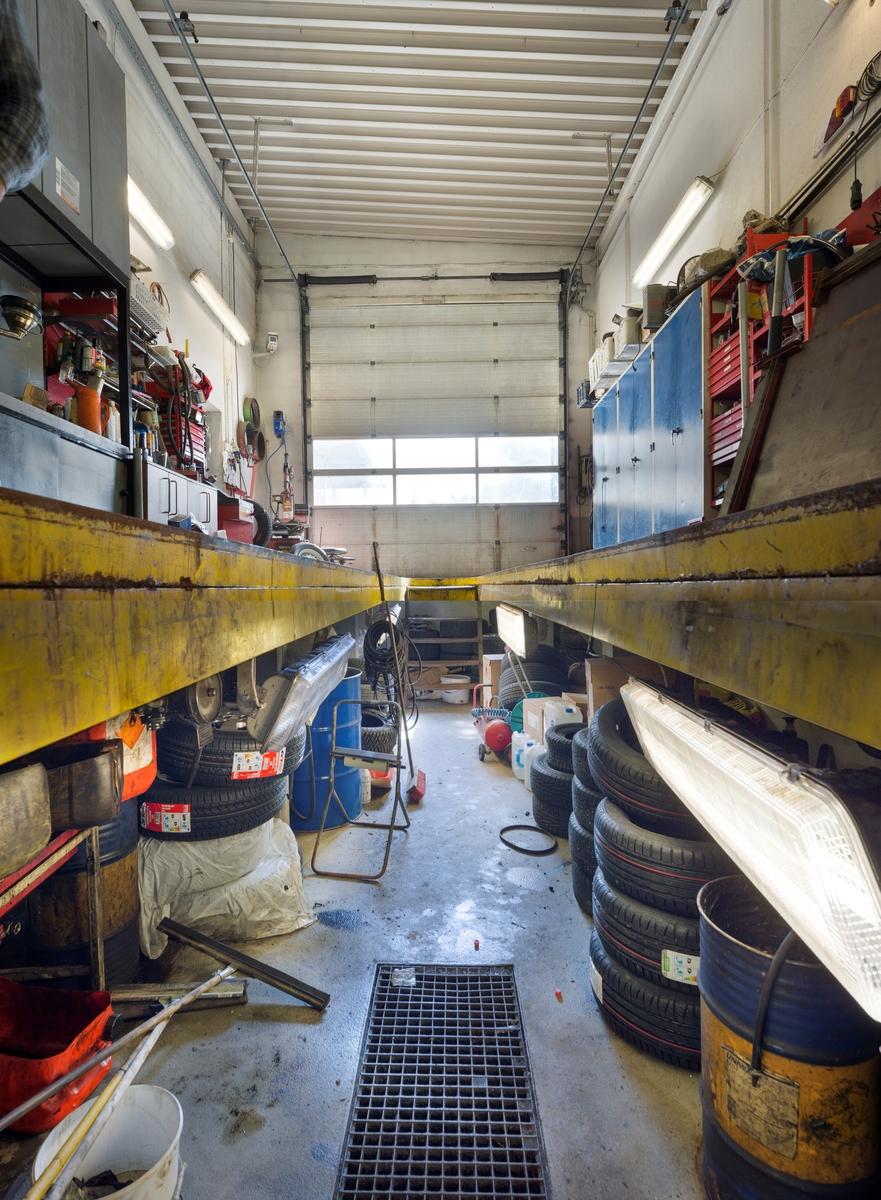 Statoil Hemnes. Verksted interiør nede i verkstedgraven. Dekk og oljetønner med utstyr.