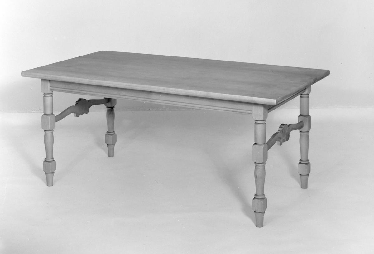 Spisebord med utskjeringar i tre.