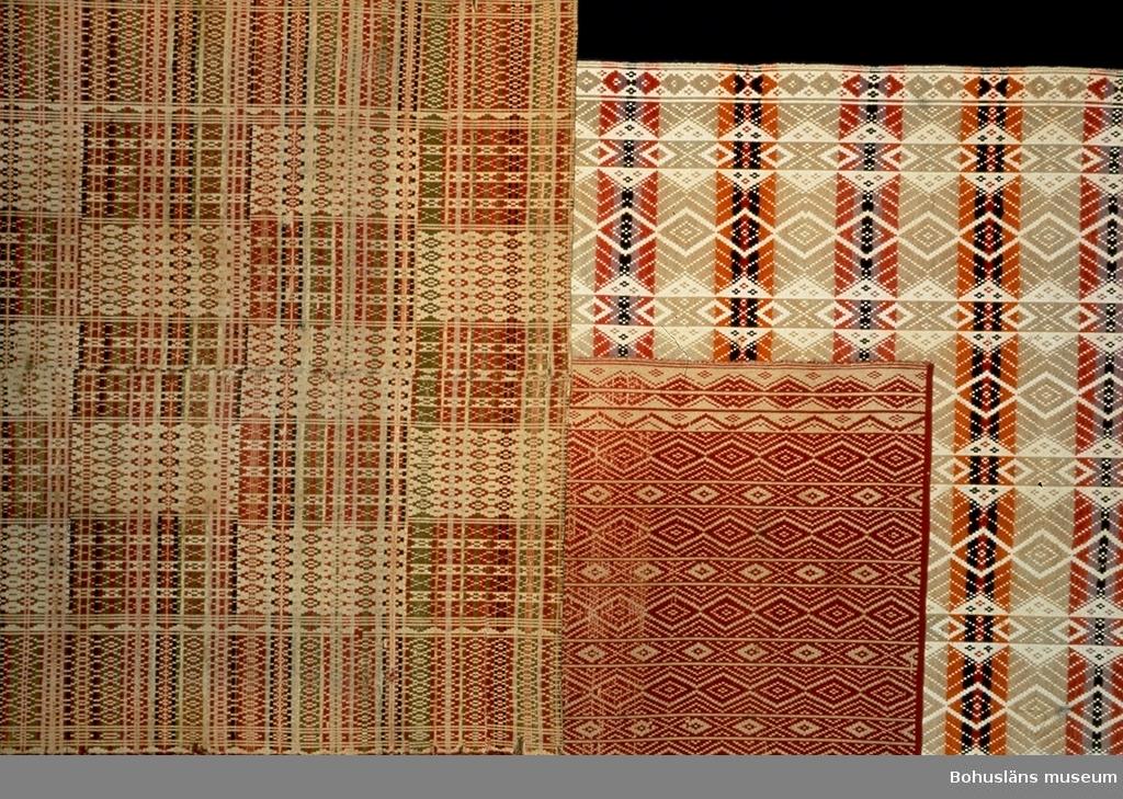 """Täcket är avbildat till vänster på föremålsfoto 3. Täcket i mitten är UM016034, täcket till höger är UM019866.  Täcke av två våder. Ihopsytt med symaskin på mitten med längsgående  söm. Varp av bomullsgarn, botteninslag av lingarn, mönsterinslag av  entrådigt ullgarn. Bottenvävens färg är ljust beige. Täcket är helt mönstrat. Längs långsidorna finns småmönstrade bårder med tätt mön ter. Innanför bårderna finns mönster i ca 27 X 25 cm stora rutor, omväxlande mörka och ljusa. I de ljusa rutorna ligger större delen av mönsterinslaget på avigsidan så varpens ljusa färg syns mer. Mönsterinslaget är inskyttlat i en oregelbunden randning med smala ränder i färgerna bruntonat gulrött, rött, mycket ljust blåtonat  grått, svart, beige, gråtonat gulgrönt. Längs långsidorna bildar öglor av inslaget en ca 1 cm kort frans. Kortsidorna är fållade med sy- maskin. Tillverkningstiden angiven med detta som utgångspunkt.  Spegeltäcke är en bohuslänsk benämning på denna typ av upphämtatäcke med rutor så kallade speglar. Kallas också Västgötatäcke och såldes av kringvandrande knallar. Men """"spegeltäcken"""" har även vävts i Bohuslän.  Flera revor, bl a en stor i ena kanten. Flera små hål. Två långa lagningar av revor nära ena kortsidan. En liten stoppning mitt på. Smutsigt, en svart fläck och flera bruna.  Literatur: Berg, Kerstin. Selma Johansson - väverska och hembygdsforskare i Södra Bohuslän, Skrifter utgivna av Bohusläns museum och Bohusläns hembygdsförbund Nr 41, Uddevalla 1991, sid 178-186.  Lychou, Kerstin, Hemslöjd och folkkonst i Bohuslän, Warne förlag AB, Partille 1996, sid. 156-160.  Sekora, Ann-Britt, Upphämta i Bohuslän (uppsats vid enstaka kurs i vävning Vt 1981, Institutionen för slöjd och hushållsvetenskap, Göteborg).  För ytterligare uppgifter om givaren se UM016001."""