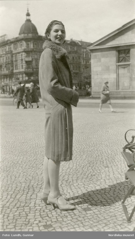 Berlin. Ung leende kvinna i kappa med pälskrage.