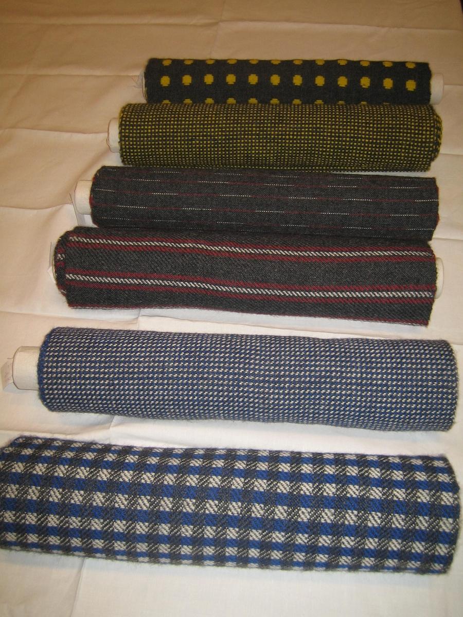 Tygprover av sex olika rullar med ulltyger. Monterade på gasklädda papprullar. Vävda med 2-trådigt ullgarn i olika färger