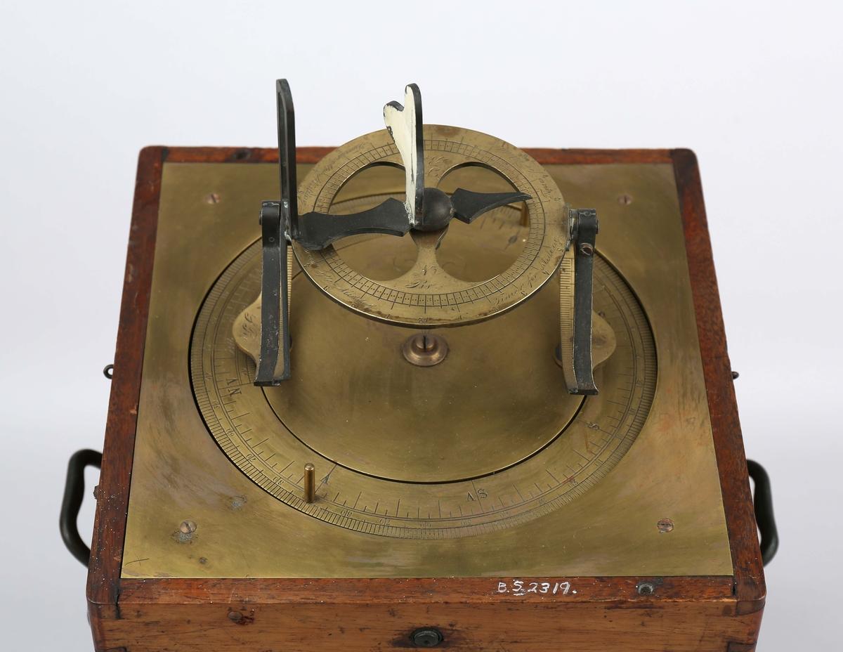 Kurskorrektor. Peileskive i messing montert på mahognykasse med to håndtak på sidene og uten lokk. Øverste del av kasse kan beveges sideveis.