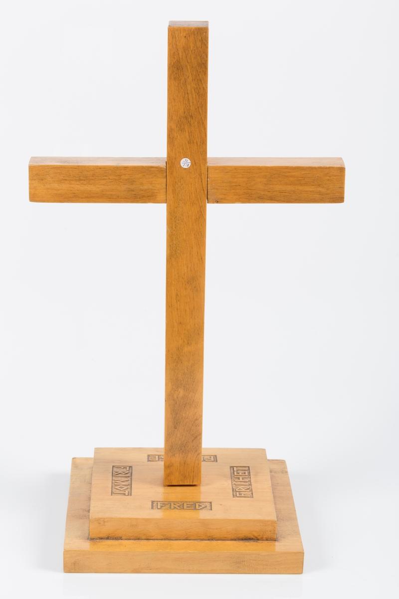 """Kors i lakert tre bestående av tre deler. Selve korset er i to deler som er innfelt i hverandre. I tillegg er det en kvadratisk fot bestående av to flater i forskjellig størrelse limt på hverandre. I midten er det kvadratisk innfelling til korset. På fotens øverste flate er det på hver side skåret inn tekst, henholdsvis """"FRED"""", """"FRIHET"""", """"FRELSE"""", """"FRI MOT""""."""