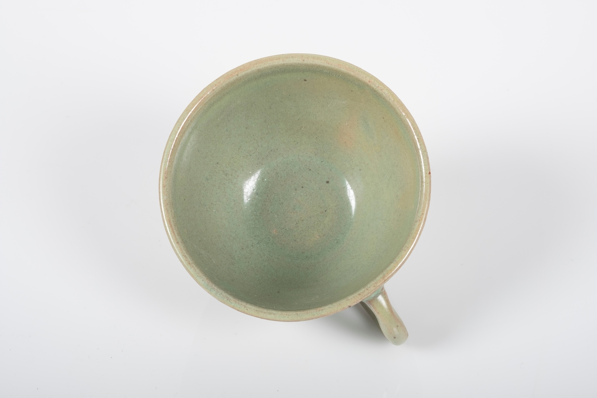 Kopp i keramikk med grønn lasur. Buet hank. Spor etter tre knotter på bunnen, usikker funksjon. Bunnen har matt overflate.