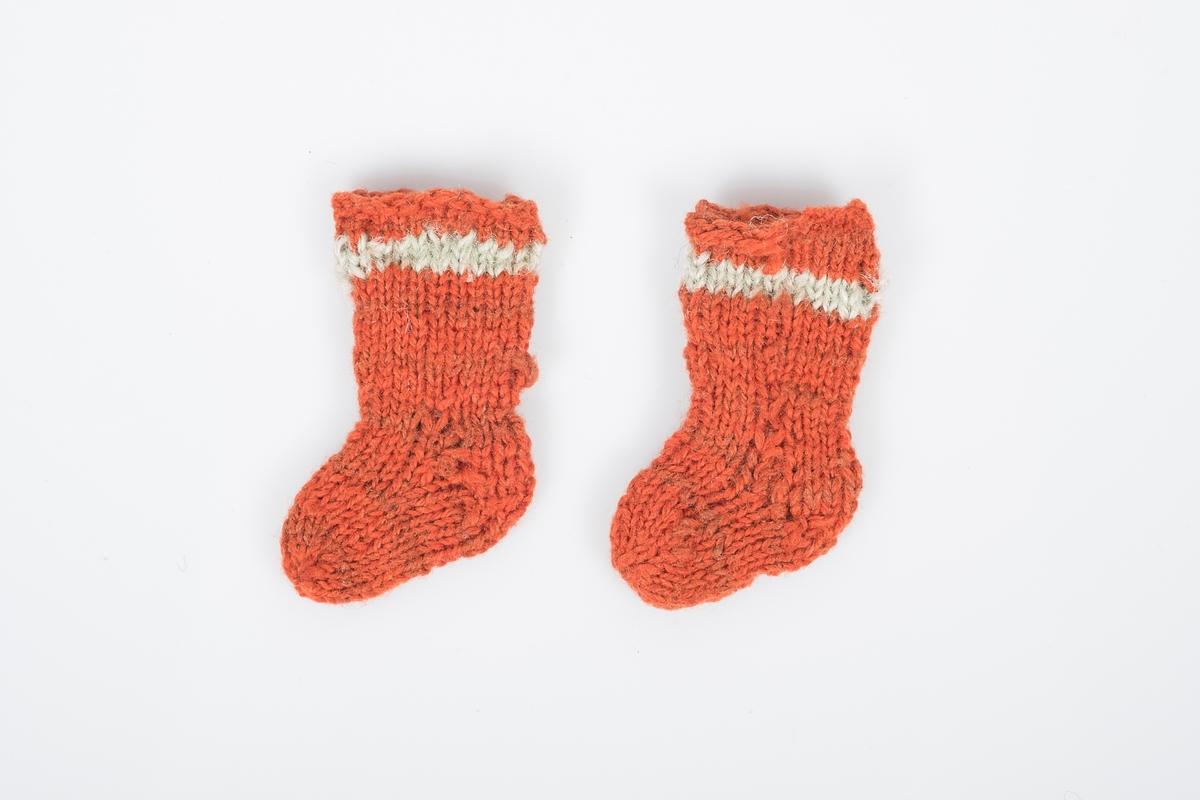 Et par bittesmå strikkede ullsokker. Sokkene er oransjerøde med en lys stripe øverst og nøen brunrøde striper lenger ned.
