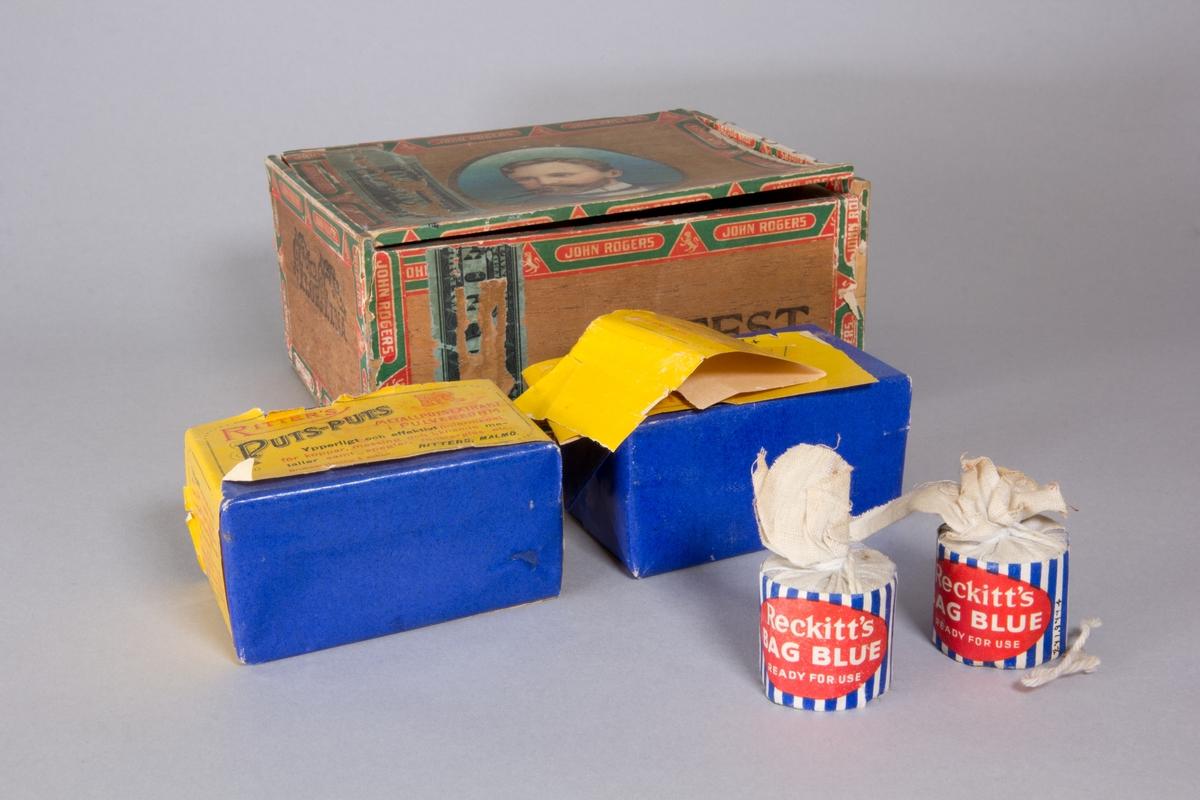 Putsmedelsask bestående av cigarrlåda av trä med fällock från Texas innehållande putsmedel: 2 st oöppnade rektangulära förpackningar av Ritters Puts-Puts med blått omslagspapper och gul banderoll samt 2 st oöppnade cylindriska förpackningar av Reckitts Bag Blue av tunn väv och banderoll randig i blått och vitt samt oval röd etikett med vit text.