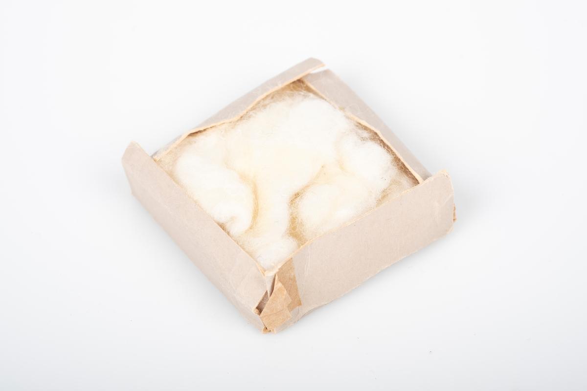 Bunn til eske i papp, med bomull i. Bunnens kanter kan brettes ut.