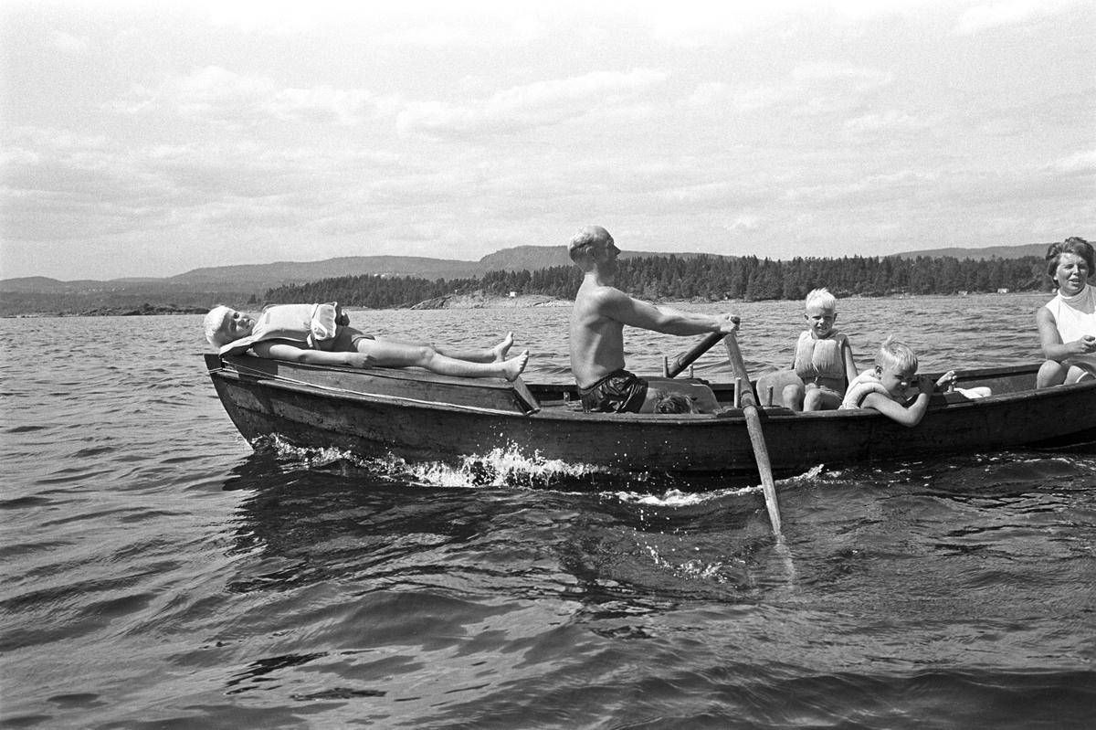 Erik Damman, reklamekonsulent fra Oslo, ferierer i båt med familien i Oslofjorden. De skal ro 10 - 12 mil i løpet av 8 - 10 dager, og går i land på små holmer som fjorden har mange av. Erik Damman ved årene. Ragnhild Damman sammen med Are (8) og Brede (5). Rein (10) ligger på soldekket forut.