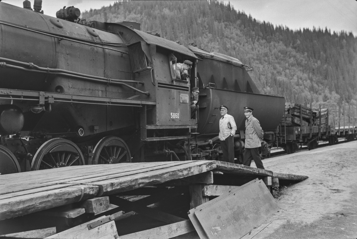 Underveisgodstoget fra Trondheim til Hamar over Røros, tog 5712, har stoppet på Kotsøy stasjon. Lokomotivpersonale og konduktørpersonale konfererer. Toget trekkes av damplokomotiv type 63a nr 5860.
