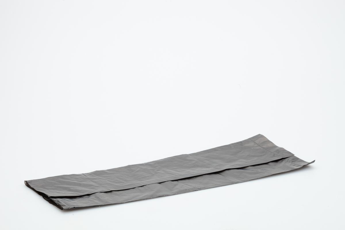 En sort hundepose i myk plastikk. Ingen hank.  Gjenstanden er samlet inn i forbindelse med Hundeprosjektet 2006-2007 Husdyr på museum - Et fellesprosjekt i Akershusmuseet 2007