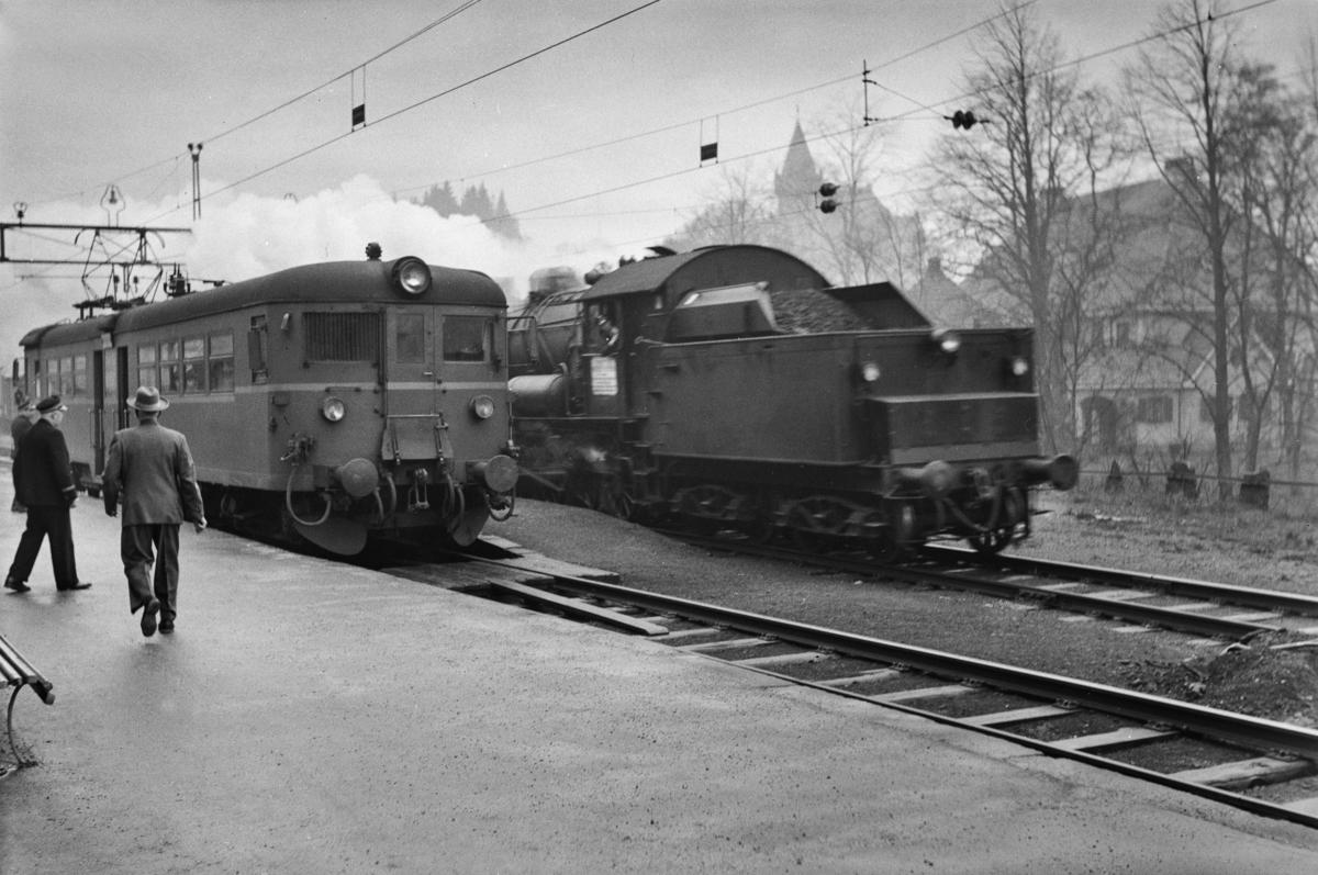 Kryssing på Fjøsanger stasjon mellomllokaltog reting Voss, tog 624, og godstog til Bergen, tog 5501. Godstoget trekkes av damplokomotiv type 33a nr. 300. I lokaltoget elektrisk motorvogn Bmeo 65.
