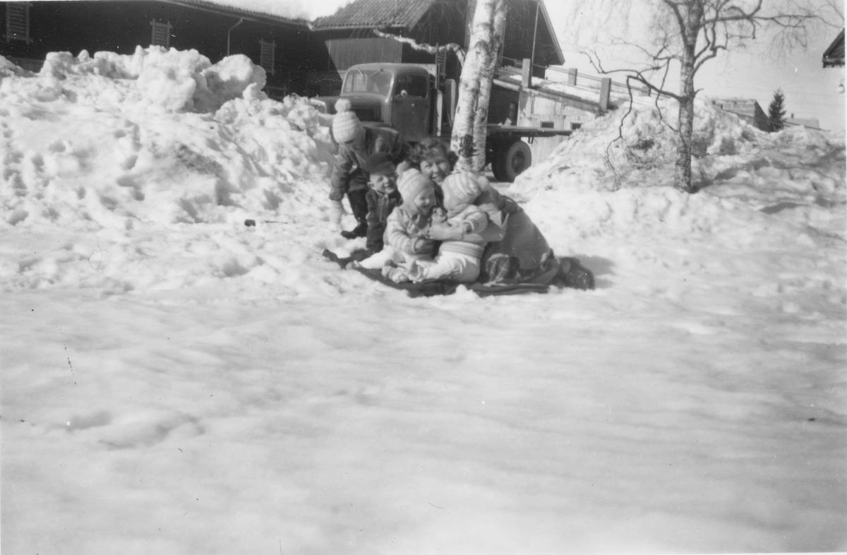 Randi Braate og 4 små barn leker ute i sneen.