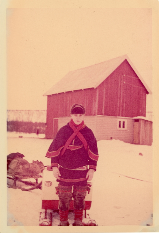 18 år gammel Are Ingvald Hallonen står foran snøscooteren med en kjelke. Fjøs i bakgrunnen. Are Ingvald har på seg luhkka og samisk belte. På føttene har han skaller med skallebånd. Året er 1966.