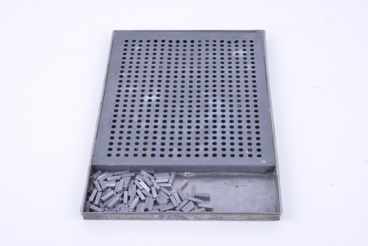 Rektangulært brett av bly med hull for brikker. 90 avlange metallbrikker.