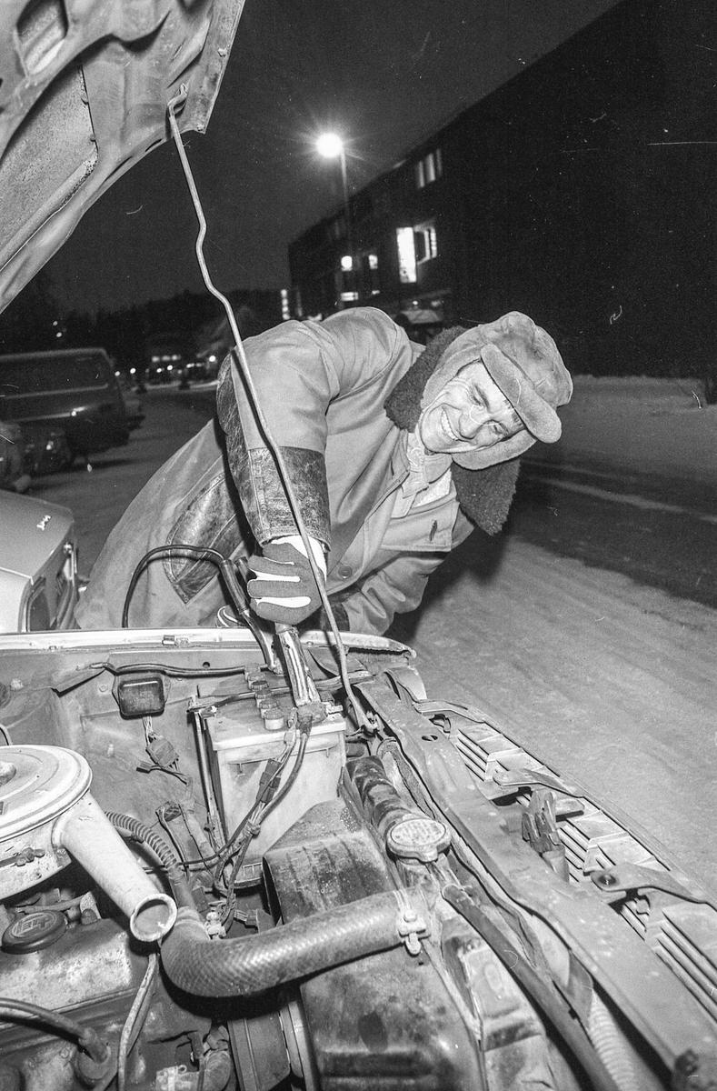 Startvansker i kulda. Mann med skinnlue bruker startkabler fra annen bil.