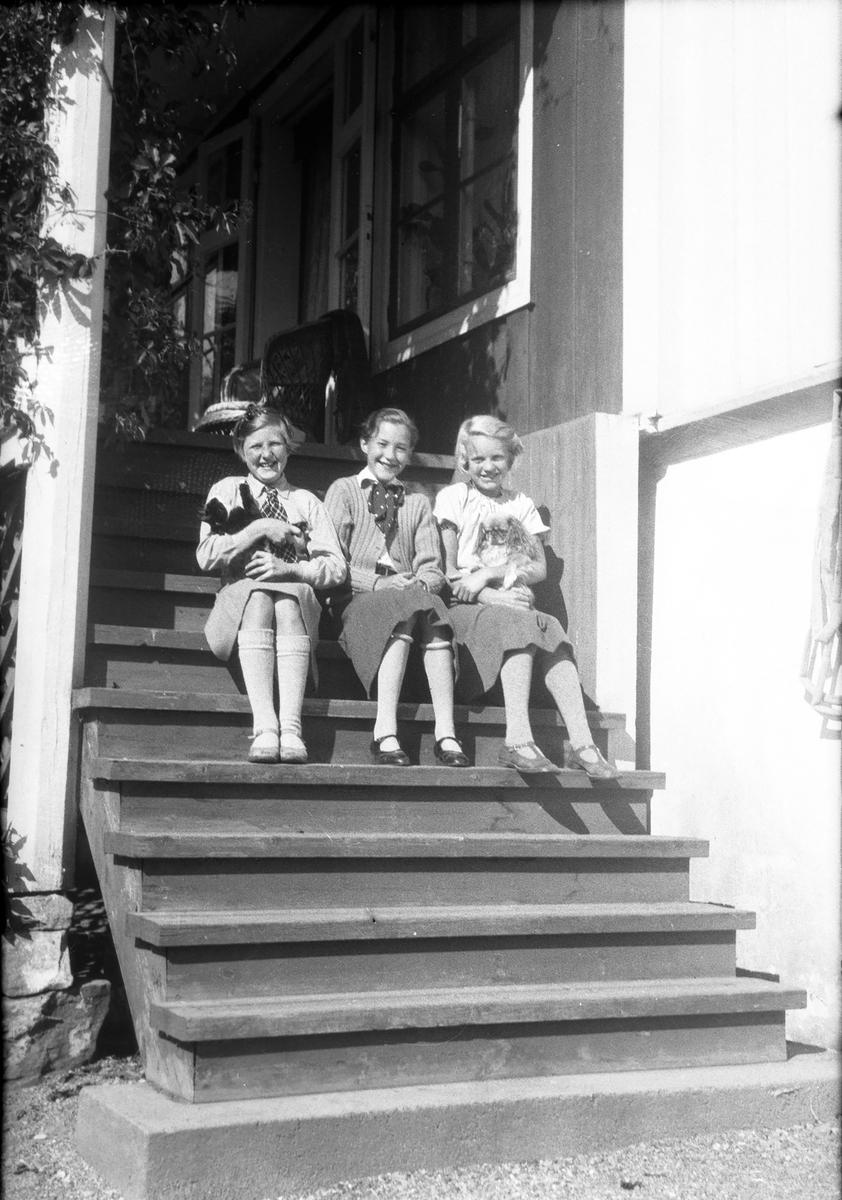 Tre jenter sitter på trapp