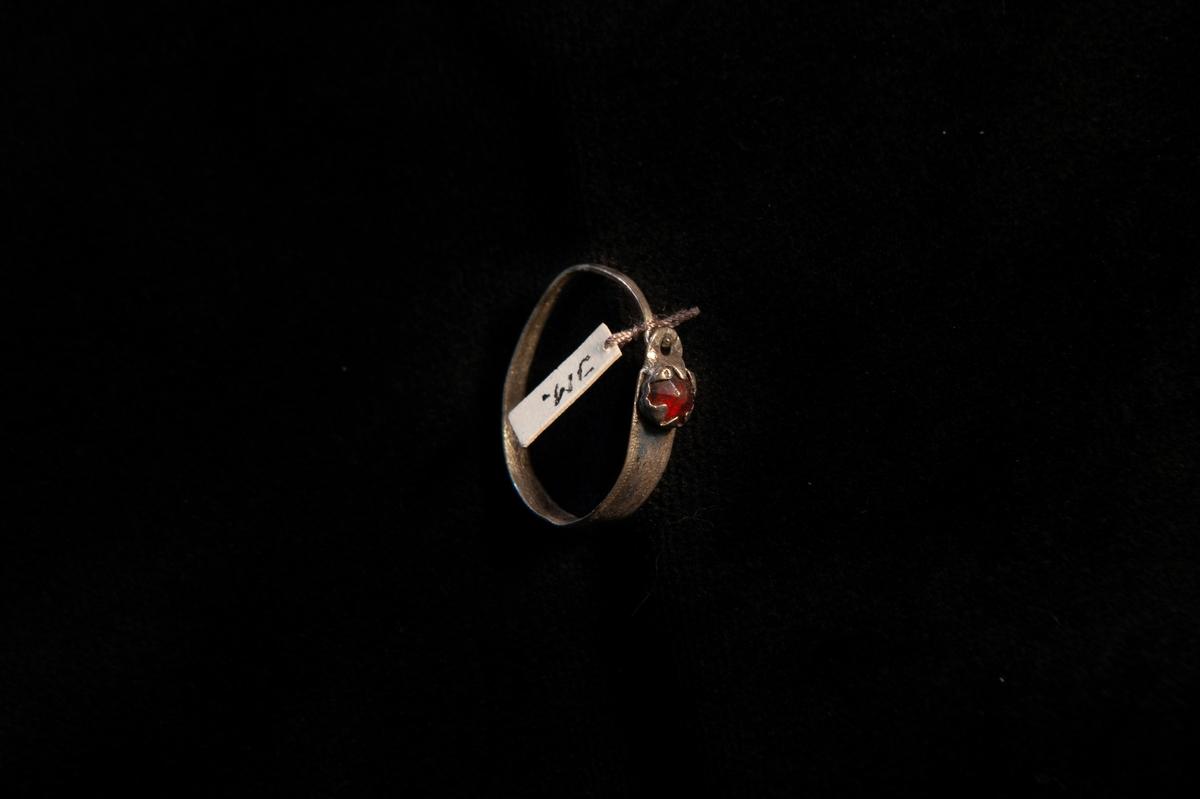 En oval örring av metall (silver ?) med graverad dekor och infattad röd glassten.Allmogemodell.