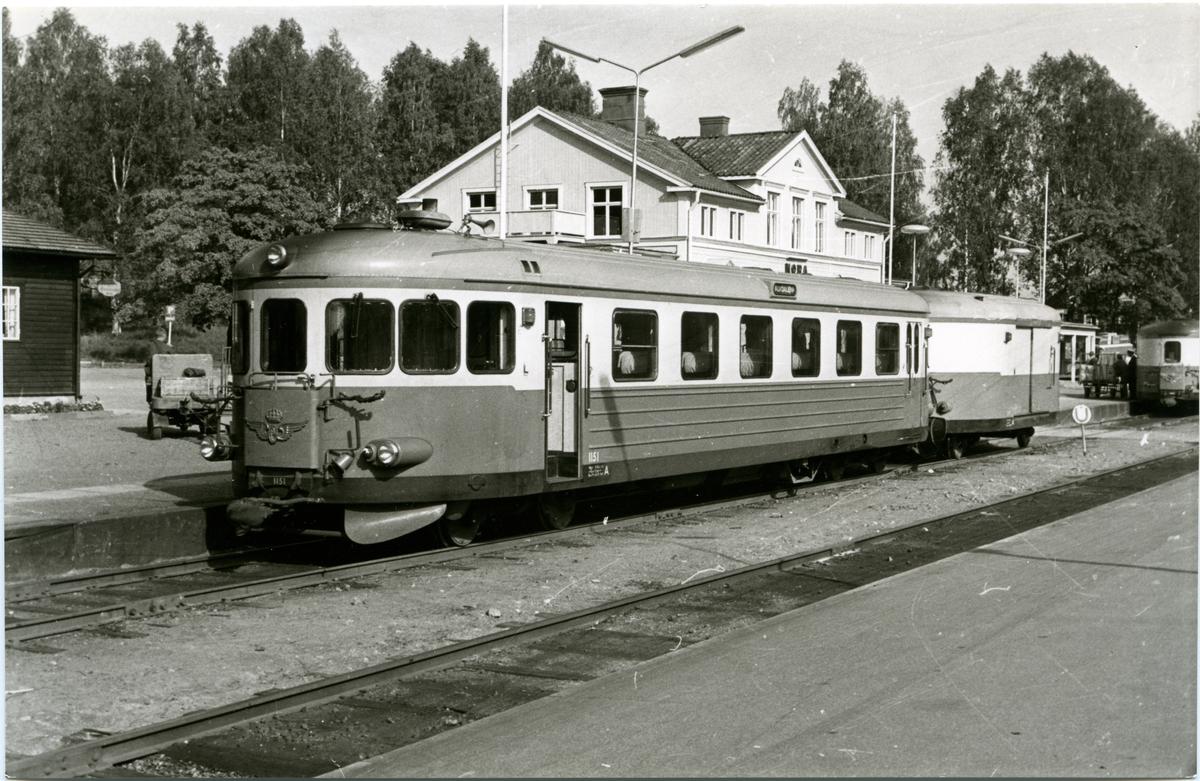 Stationen omb. 1929 . MVJ, anlagd 1891. 1896 öppnades Mora - Mora Noret. Stationshuset ombyggdes och moderniserades 1930. Tre bostadshus med vardera fyra lägenheter uppfördes omkring 1920. Tvåvånings stationshus i trä  MVJ, Mora - Vänerns Järnväg. SJ YBo7 1151