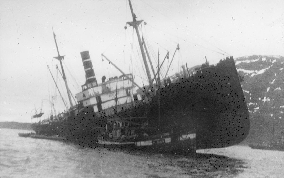 Dampskip med baugen i været. Tre mindre farkoster ligger langs skipets langside.