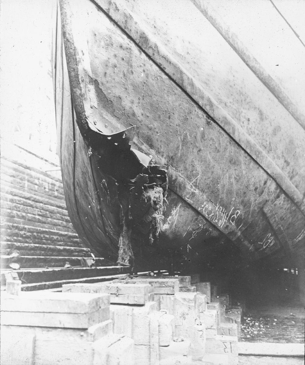 Skipsskrog i tørrdok, baugen løftet opp på blokker.