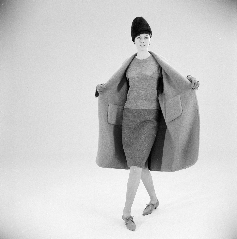 """Kvinnelig modell i kåpe, drakt og lue. Fra Norsk Dameblad v/ Lillemor Breien / Tommie. Fra serie til artikkelen """"Tilbehør som teller"""" trykt i nr. 11, 1964.."""