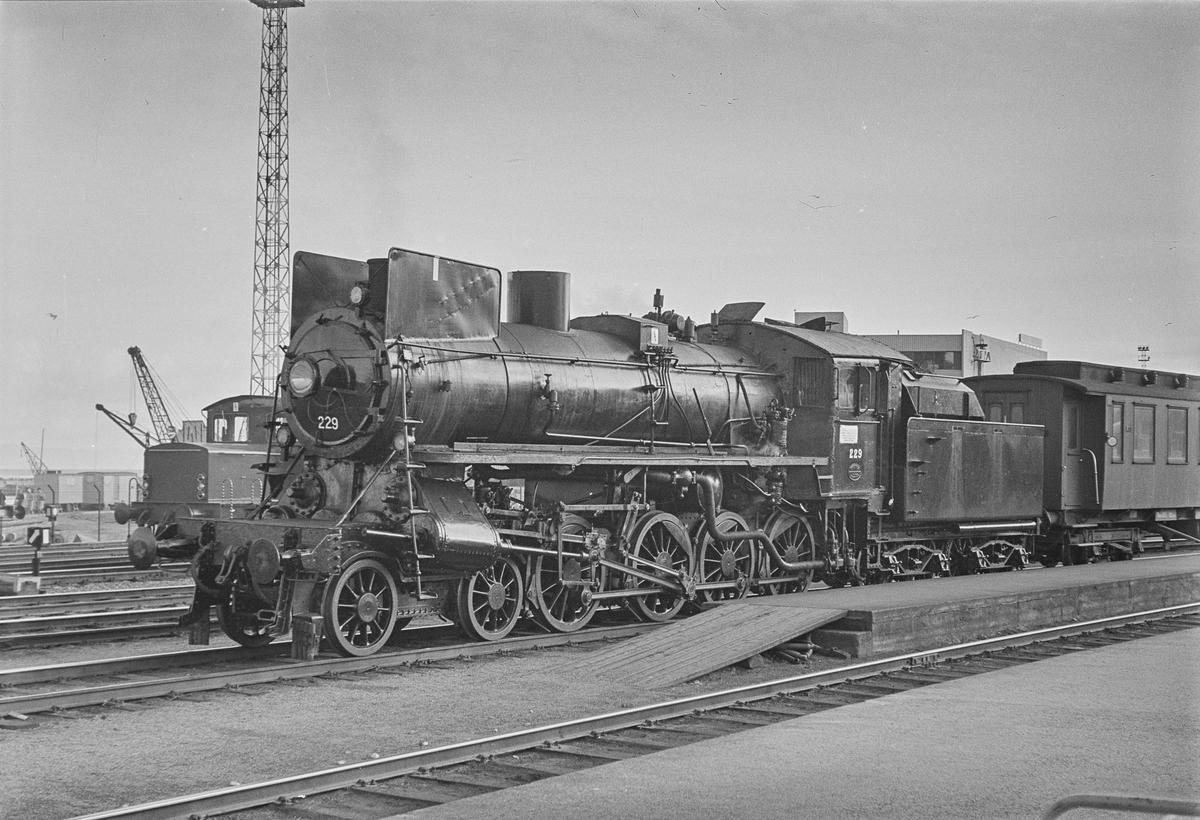Persontog på Trondheim stasjon. Toget trekkes av damplokomotiv type 26b nr. 229.