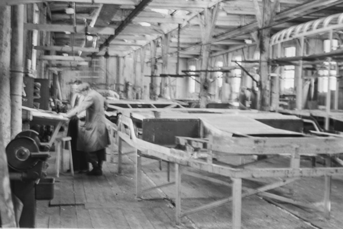 """Fabrikkhallen på Strømmen Verksted. Bygging av vognkasser til Oslo Sporveiers sporvogn type """"Gullfisk"""" pågår."""