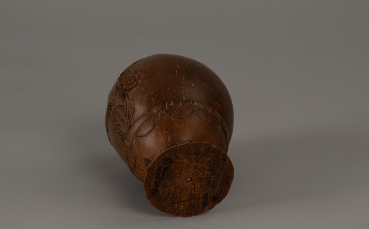 Sparebøsse, sjømannsarbeid, 1894.   Kokosnøtter,  med relieffdekor og eiernavn.   Foten laget  av et kokosnøttsegment, med tungebord  langs kanten. Bøssen er en hel nøtt,  brunpolert, med hull til penger i toppen, på den ene side to blomster  grener og tekst.