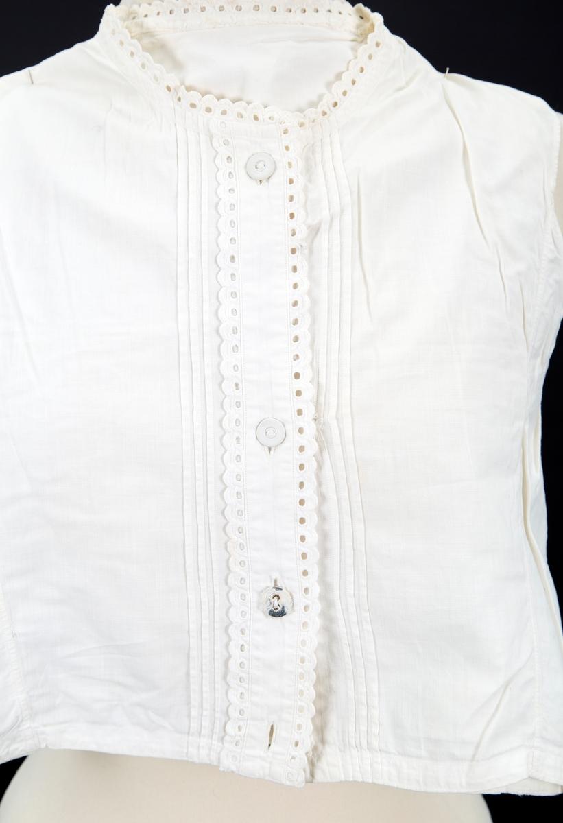 Knappestolpen og halslinning kantet med bånd med hullsøm og tungekant. tre smale legg på hver side av knappestolpen. 4 knapphull, 3 lerretsknapper - en knapp mangler en knapp slitt. Liten revne mellom legg på v. forstykke reparer med håndsøm.  forstykket har 4 bredder, bakstykket 3 bredder. reparasjoner i nakken med bl. a påsydd lapp