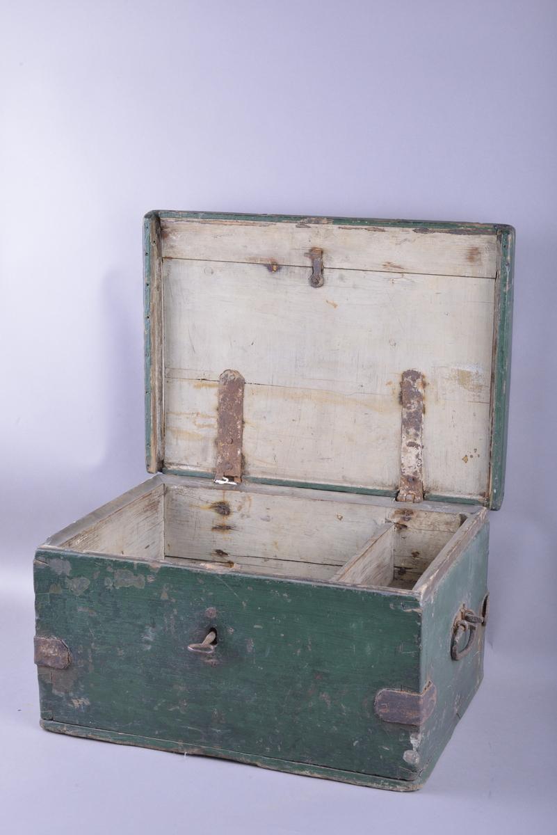 Rektangulær formet kiste med lokk. Kisten har en låsemekanisme i front, med tilhørende nøkkel. Lokket kan vippes opp, og er festet med hengsler på baksiden. Lokket kan ikke fjernes. På hver kortside av kisten er det festet to kraftige metallhåndtak. Kisten er forsterket med beslag både i lokket, og på hver festekant av kistesidene. Utsiden av kisten har malt overflate.  Innsiden av kisten består av et stort rom, samt en ledikk på høyre side. Innsiden av kisten framstår behandlet med maling/lakk. Kisten er tom.  Kisten bærer preg av tiden, metallbeslagene er svært rustet og malingen er flekket. Hengselet som fester lokket til kisten (venstre) er løst.