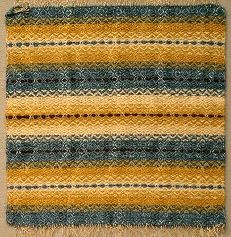 Dukprov med frans.Varp: lingarnInslag: ullgarn i blått, gult och naturvitt Under 2:a världskriget (kristid) fick industrifärgat garn endast användas till nyttovävar. Därför vävdes det mycket med ofärgat och växtfärgat garn.Hos väverskorna var det populärt att väva dessa ylledukar då det var ont om arbete och de gav bra betalt, 1.75 kr per meter.Hemslöjden fick då och då under denna period besök av kontrollanter (från statlig myndighet?)  som kom för att se efter att reglerna för användningen av färgade garner efterlevdes.
