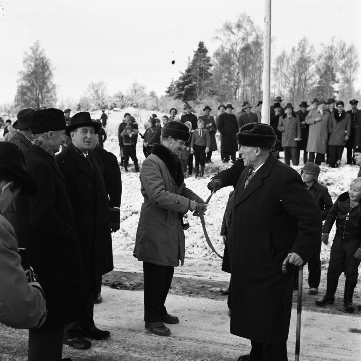 Bandet klipps. Örebrovägen öppnas efter ombyggnad. En stor publik, de flesta män, har samlats.  Det är vinter och snö.