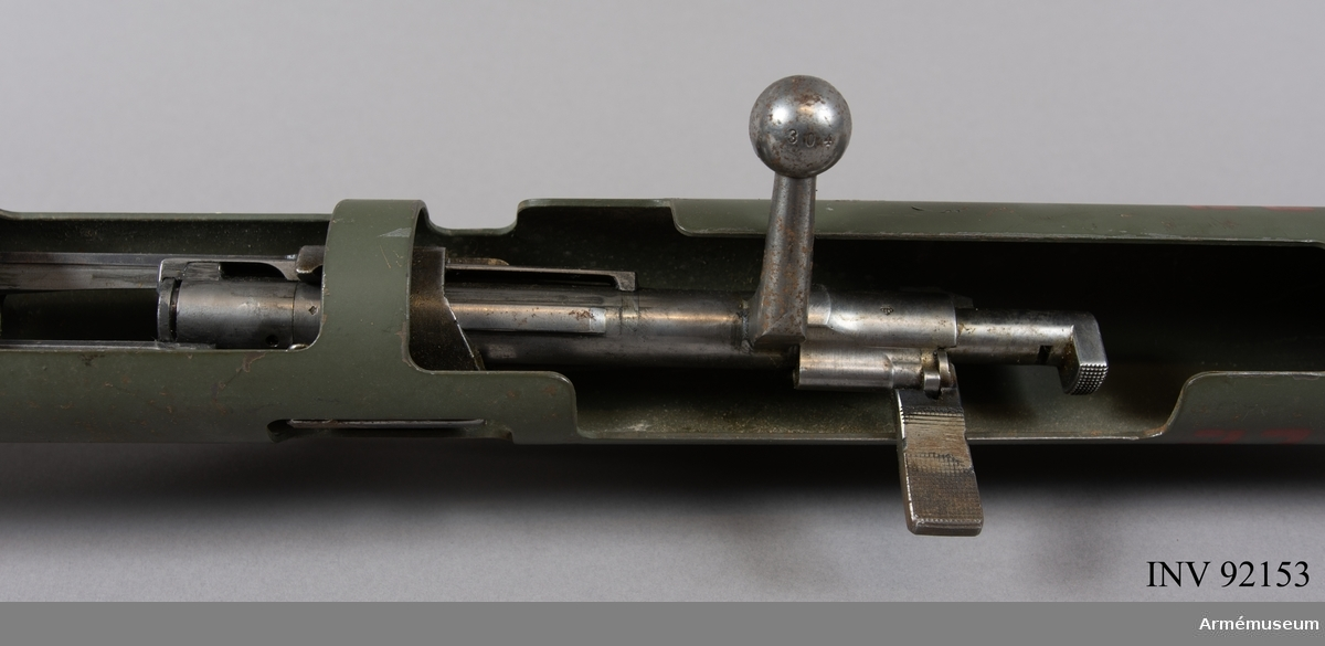 """Övningsvapen 1 består av ett stålrör med en längd av cirka 120 cm och 5 cm i diameter. Den bakre änden är vidgad till en tratt och främre änden försedd med träkropp. Inuti stålröret finns en karbinpipa med mekanism inbyggd. Mellan träkroppen och tratten sitter ett sikte, avfyringsarm och säkringsslid. På träkroppen (den grövre konen) finns ett sikte som är justerbart i höjd och sidled.   Karbinpipan är snedställd i stålröret så att sikte och korn som överensstämmer med det skarpa pansarskottets, är avpassade för ett skjutavstånd på 7,2 meter. Stålröret är uppslitsat så att mekanismdetaljerna är lätt åtkomliga. Mekanismens säkringsklack har förlängts 20 mm.   Till 6,5 mm övningsvapen 1 för pansarskott användes endast 6,5 mm kammarpatron m/1912.  Vid iordningsställande fälldes siktet ned och karbinen laddades.  Vid skjutning hanterades övningsvapnet som ett skarpt pansarskott förutom att karbinmekanismen först måste osäkras.   Vård: För övningsvapnets vård gällde """"Allmänna bestämmelser för vård av tygmateriel och am"""" i Sold1 Mtrl."""