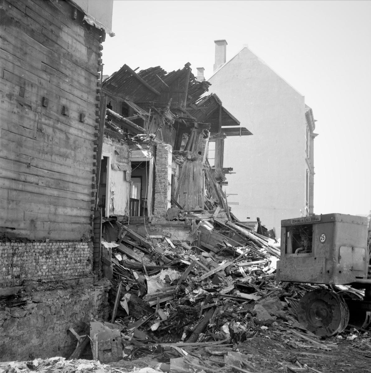 Bybebyggelse. Riving av en bygning i Haugesund sentrum. Bygninger på begge sider. Utsikt til sundet. Gravemaskin i arbeid. Brolagt gate. Bestilt av Skipsreder Amlie