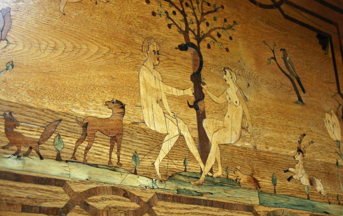 Bordet er utført i eik og innlagt med forskjellige sorter naturlig farget tre, samt innfarget treverk og tinn og står på cabrioleben med putefot. Sargen er profilert og går opp i en bue på midten. Sargen har tre skuffer, to skuffer på sidene av buen og en smal en over. Den midterste skuffen har motiv av fire trær på grønn bakke innenfor en ramme av intarsia i mørkt tre. Sideskuffene er dekorert med like rektangulære panel med motiv av to hus og trær på grønn bakke. Det samme motivet finner vi på sidesargen. Alle feltene er innrammet av en bred stripe intarsia som gjentar skuffenes kontur. Bordflaten er dekorert med motiv av syndefallet, og viser Adam sittende til venstre og Eva til høyre. Mellom dem sees kunnskapens tre med frukter og slangen. I det venstre hjørnet øverst ser vi en engel med sverd, og i det øvre høyre hjørnet sees en fugl på gren. Under Adam og Eva er en grønn bakke med stor blomst ytterst til venstre og rev, hund, kanin og dåhjort på høyre side. Revens og Adams øyne er av tinn. Motivet er innrammet av et dobbelt, kryssende båndmotiv innenfor en bred stripe i mørkt tre som følger bordflatens kontur.