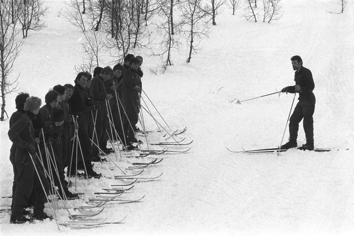 Befalsskoleelever oppstilt på ski. Offiser instruerer.