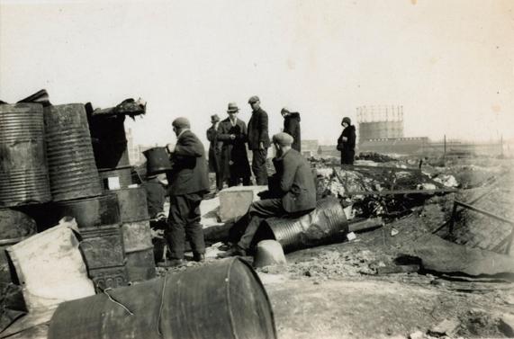 """Ansamling av menn og to kvinner ved tønnehus/boligbrakke i """"Ørken Sur"""", Brooklyn NY, ca 1929-1935."""