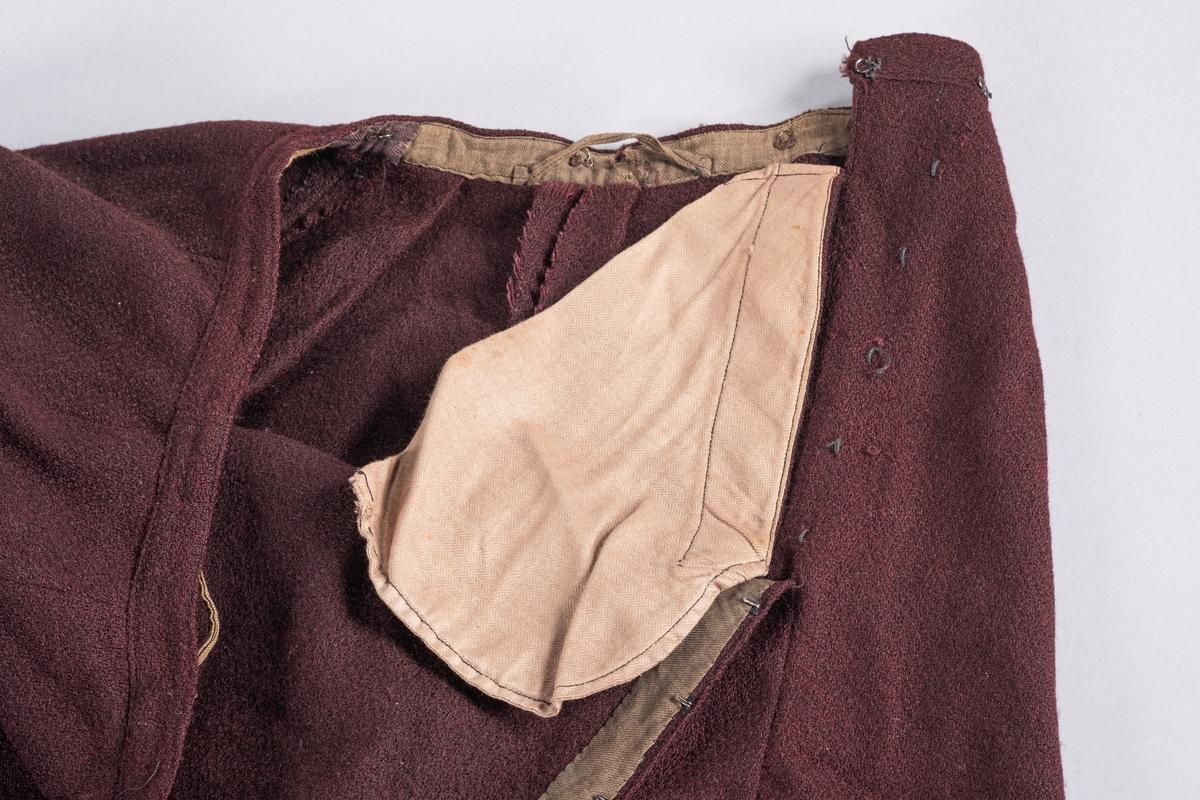 Lilla skjørt i ull, del av todelt kjole. På innsiden av livet er det 8 små metallhemper jevnt fordelt, for å feste skjørt og kjoleliv sammen. Det er også to større hemper av stoff i hver side av skjørtelinningen. I skjørtelinningen er det en splitt for på-og avkledning. I splitten er det sydd inn 5 hekter, og disse festet i 5 hemper av tråd på utsiden av skjørtet. Midjevidden kan reguleres med en hekte på innsiden av linningen, som kan festes i en av to vannrette hekter på utsiden. Skjørtet har en brun lomme på innsiden for oppbevaring. Nederst på innsiden av skjørtet er det en bred fôret kant, en forsterkningskant, med et påsydd svart bånd.
