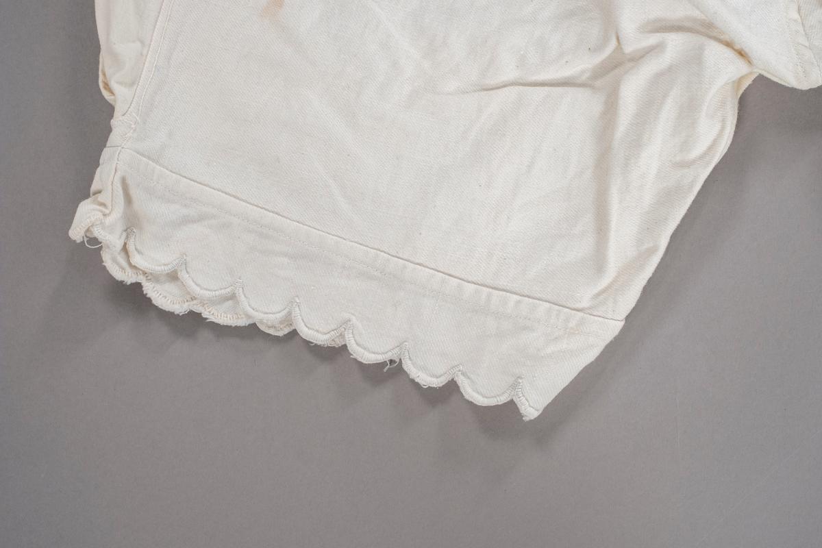 Knekort underbukse med tungekant nederst. Den har åpning i sidene som lukkes med knapper.  Den er utvidet i livet ved innfelling av tøystykker. I front er det brodert initialer.