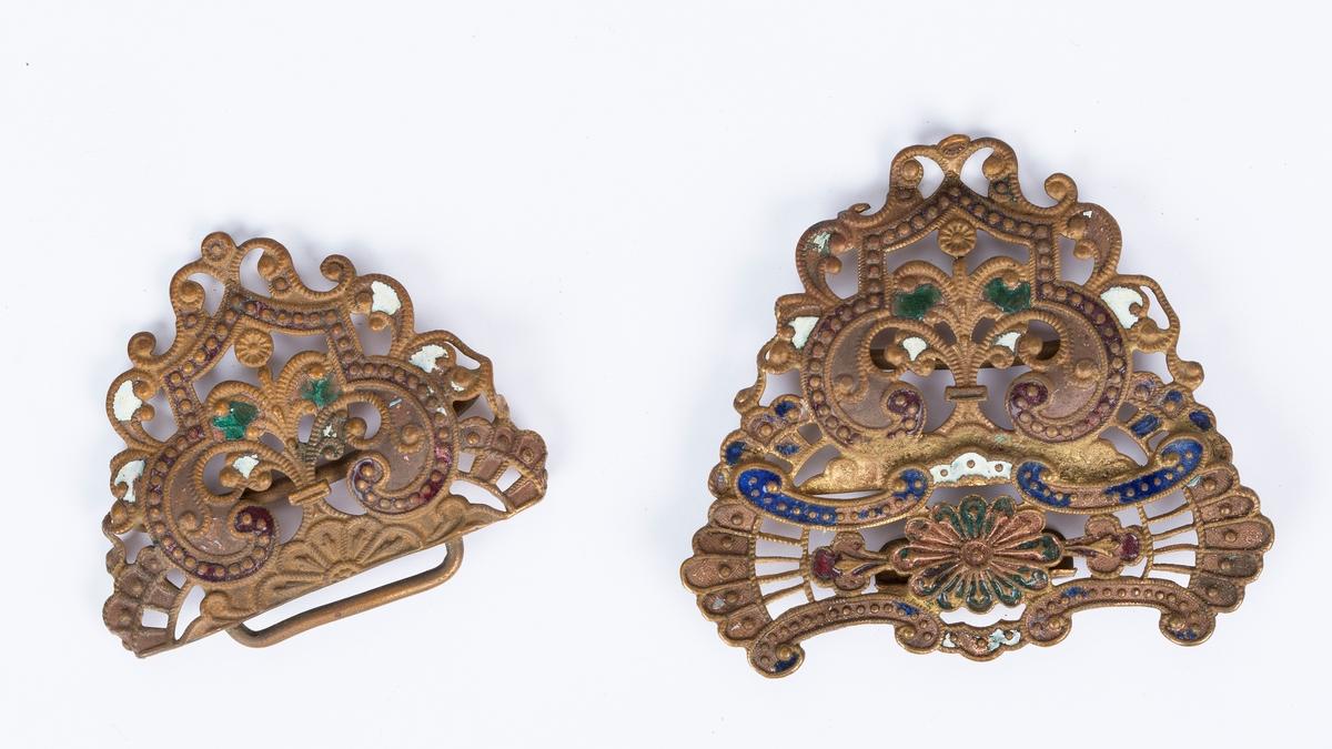 Beltespenne i to deler, hempesepenne i kobber med emalje i blå, grønn, rød og hvit. Symmetrisk, barokkinspirert. Emaljen nesten slitt vekk.