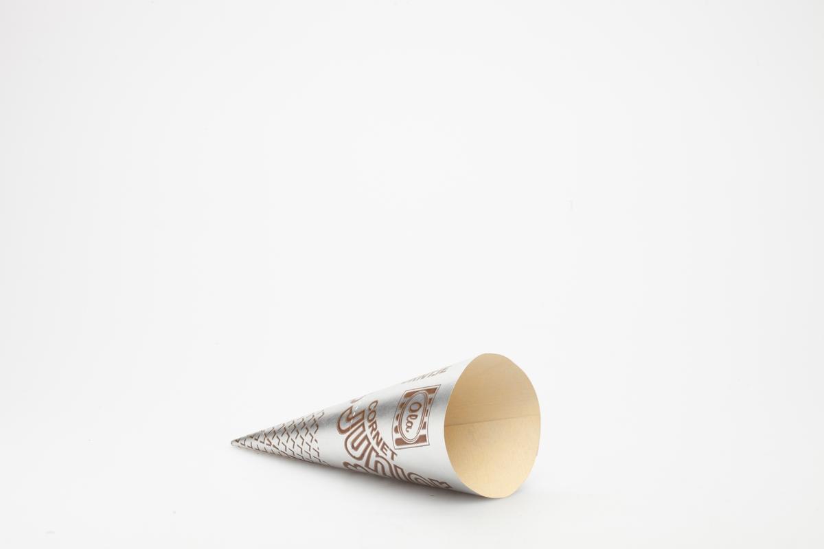 Kjegleformet iskrempapir (kremmerhus) i aluminium. Kremmerhuset er med farger på utsiden, og matt uten farge (hvit) på innsiden. Iskrempapiret har brun skrift på sølvbakgrunn. En striplete linje markerer hvor man kan rive av papiret.